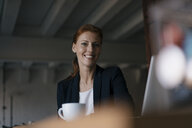 Portrait of smiling businesswoman with cup of coffee sitting at desk in office - JOSF03008