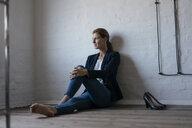 Barefeet businesswoman sitting on floor in office - JOSF03011