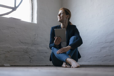 Barefeet businesswoman sitting on floor in office using tablet - JOSF03014