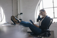 Businesswoman using tablet with feet on desk in office - JOSF03017