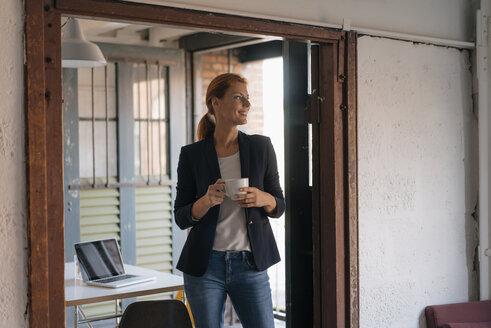 Smiling businesswoman having a coffee break in office - JOSF03020