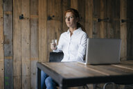 Businesswoman sitting at desk with glass of water and laptop - JOSF03029
