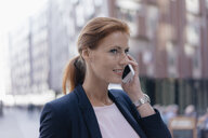 Smiling businesswoman on cell phone outdoors in the city - JOSF03041