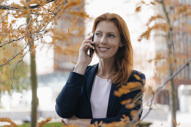 Smiling businesswoman on cell phone outdoors in the city in autumn - JOSF03044