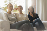 Portrait of smiling mother with two teenage girls sitting on couch at home - JOSF03053