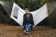 Portrait of woman sitting in hammock in garden in autumn - JOSF03065