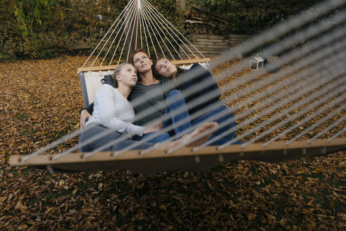 Mother with two teenage girls lying in hammock in garden in autumn - JOSF03068