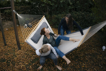 Happy mother with two teenage girls in hammock in garden in autumn - JOSF03071