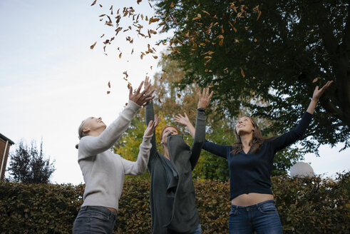 Carefree mother with two teenage girls throwing autumn leaves in garden - JOSF03074