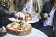 Midsection of people having breads at outdoor restaurant - ASTF02571