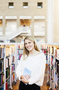 Portrait of beautiful university student standing in library - ASTF02598