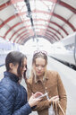 Young women using cell phone at railway station - ASTF02643
