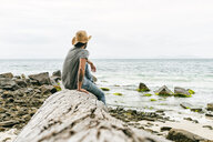 Australia, Tasmania, Maria Island, back view of man sitting on a rock looking at view - KIJF02179