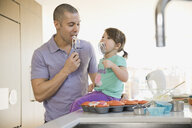 Father and daughter licking cupcake batter on beaters - HEROF06739