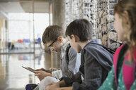 Elementary students using digital tablet in corridor - HEROF06781