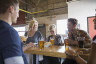Brewery waitress serving food and beer to friends - HEROF06814