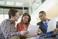 Couple reviewing paperwork with financial advisor - HEROF06874