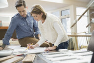 Couple looking at blueprints and wood swatches - HEROF06910
