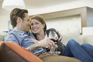 Couple drinking wine on living room sofa - HEROF06934