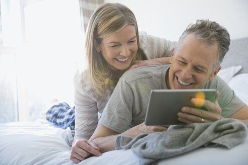 Couple using digital tablet on bed - HEROF06976