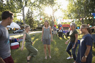 Neighbors playing with hacky sack at summer neighborhood block party in park - HEROF07015