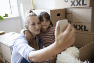 Mother and daughter taking selfie, taking a break from moving - HEROF07036