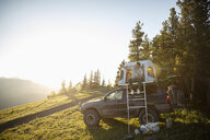Man taking selfie at SUV rooftop tent in sunny field, Alberta, Canada - HEROF07051
