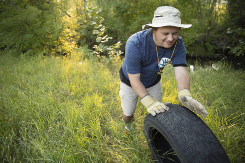 Man with down syndrome volunteering, cleaning up garbage in woods, rolling tire in grass - HEROF07066