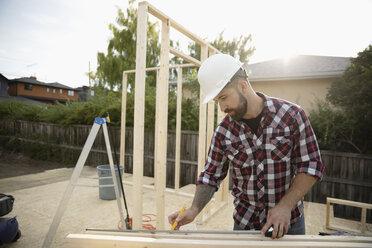 Man measuring wood planks at construction site - HEROF07075