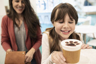 Mother and daughter ordering coffee with chocolate paw foam in cat cafe - HEROF07129