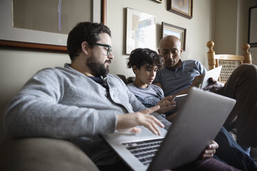 Multi-generation Latinx men using digital tablets and laptop on sofa - HEROF07165