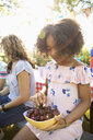 Girl eating fresh, ripe cherries at summer neighborhood block party - HEROF07198