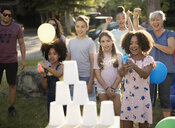 Girls playing water game at summer neighborhood block party in park - HEROF07204