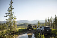 Friends enjoying overland adventure, looking at remote mountain view next to SUVs, Alberta, Canada - HEROF07231