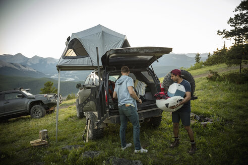 Friends camping, unloading SUV with rooftop tent in mountain field, Alberta, Canada - HEROF07237
