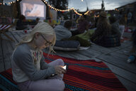 Girl using smart phone at movie in the park - HEROF07270