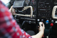 Female pilot flying airplane in airplane cockpit - HEROF07402