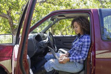 Female farmer using laptop in truck in orchard - HEROF07408