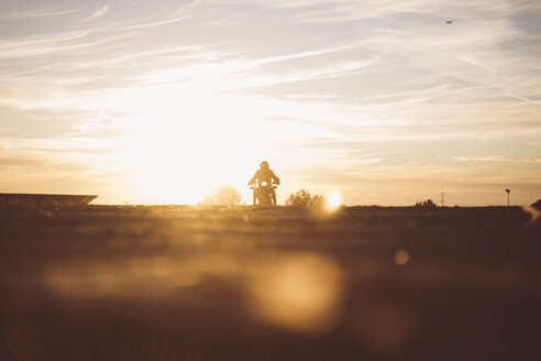 Silhouette of man riding custum motorcycle at sunset - OCMF00222