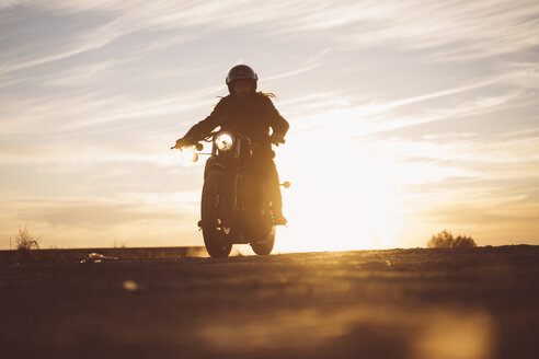 Silhouette of man riding custum motorcycle at sunset - OCMF00225
