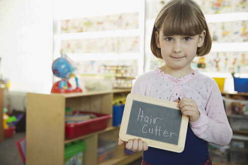 Cute girl holding slate with Hair Cutter written on it - HEROF07509