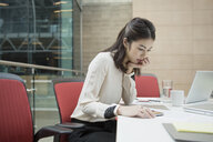 Businesswoman reviewing paperwork in conference room - HEROF07542