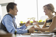 Couple toasting wine glasses at table in bistro - HEROF07596