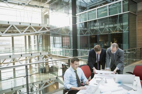 Businessmen reviewing paperwork in meeting - HEROF07623