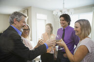 Family and friends toasting wine at home party - HEROF07629