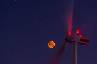 Wind wheels in front of blood moon at night - FRF00808