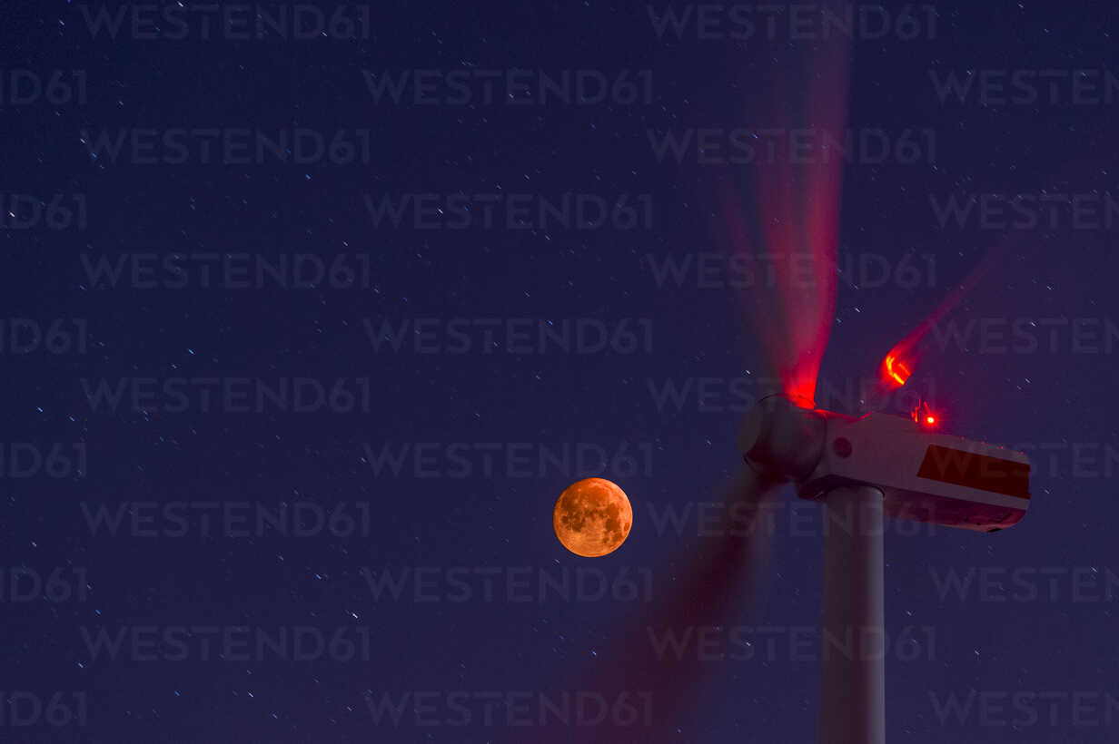 Wind wheels in front of blood moon at night - FRF00808 - Frank Röder/Westend61
