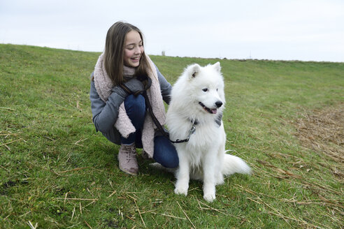 Happy girl crouching on a meadow with her dog - ECPF00249
