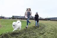 Two girls running on a meadow with dog having fun - ECPF00255