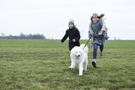 Two laughing girls running on a meadow with dog having fung - ECPF00258
